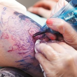 Close up of woman tattooing with many colors