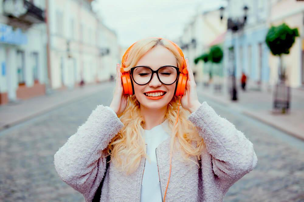 Woman listening with orange headphones