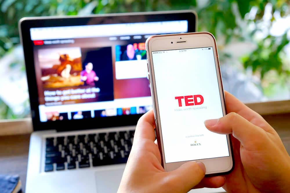 Checking TED talk on phone and laptop
