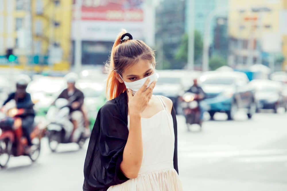Woman covering her face with a face mask, city pollution concept