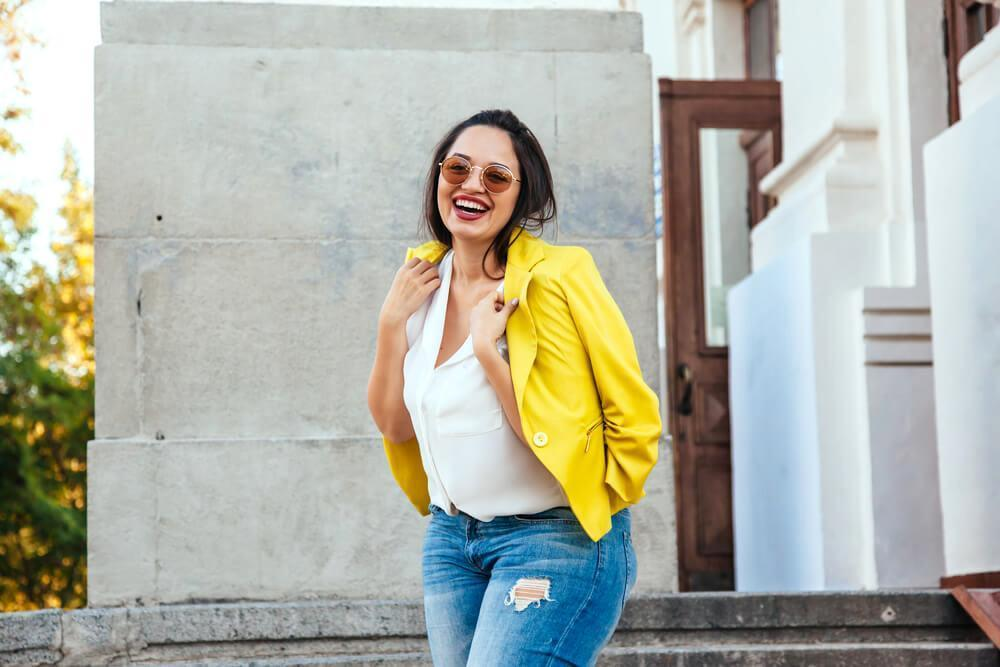Happy woman with yellow blazer and sunglasses