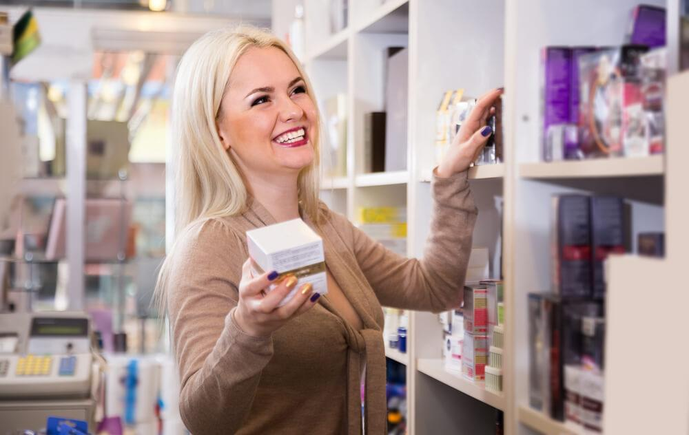 Happy smiling saleswoman holding a cosmetic product in shopping aisle