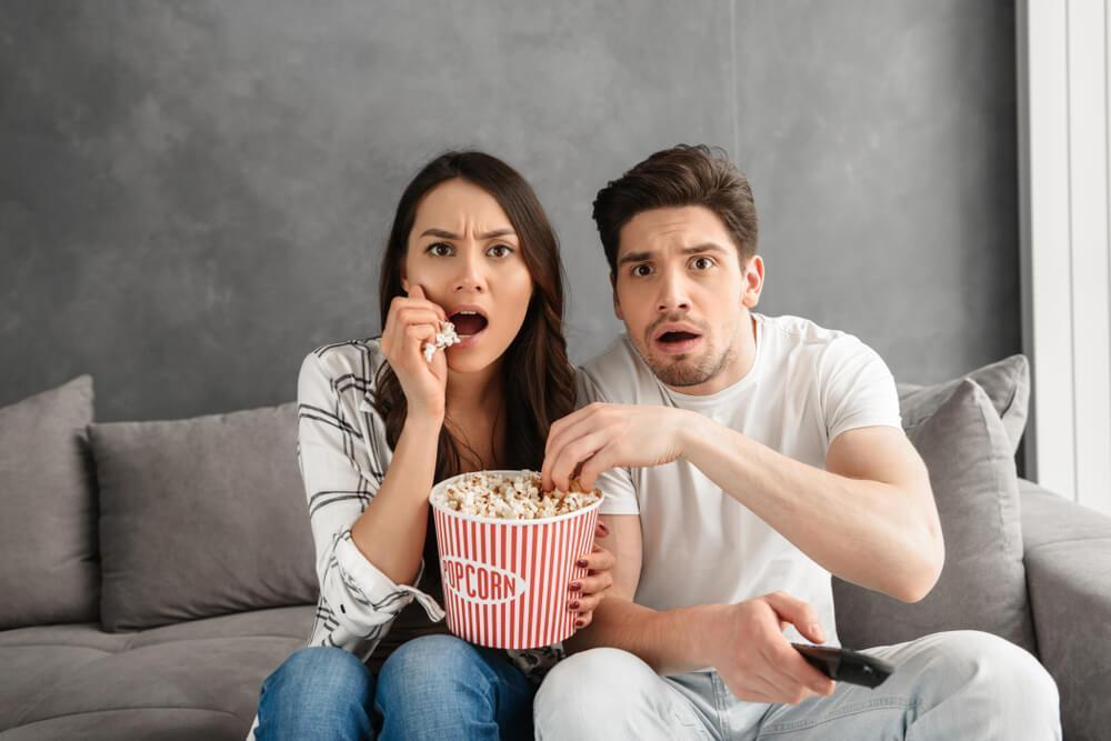 Couple watching TV at home while eating popcorn