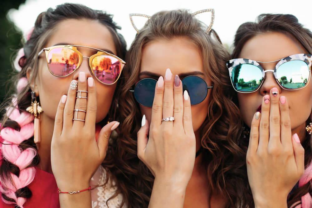 Three happy young woman showing off their nails