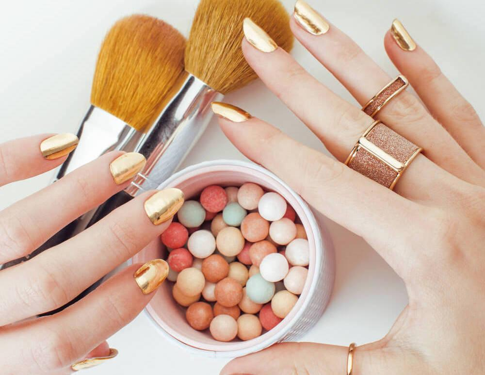 Female hands with gold nail polish