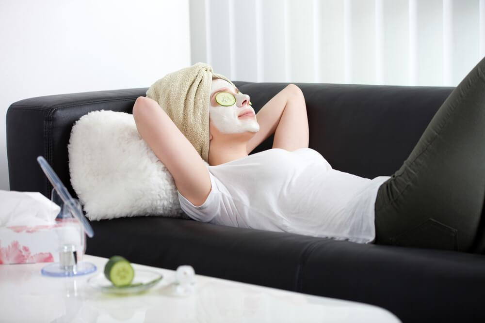 Woman on sofa with face mask and cucumber slices on eyes