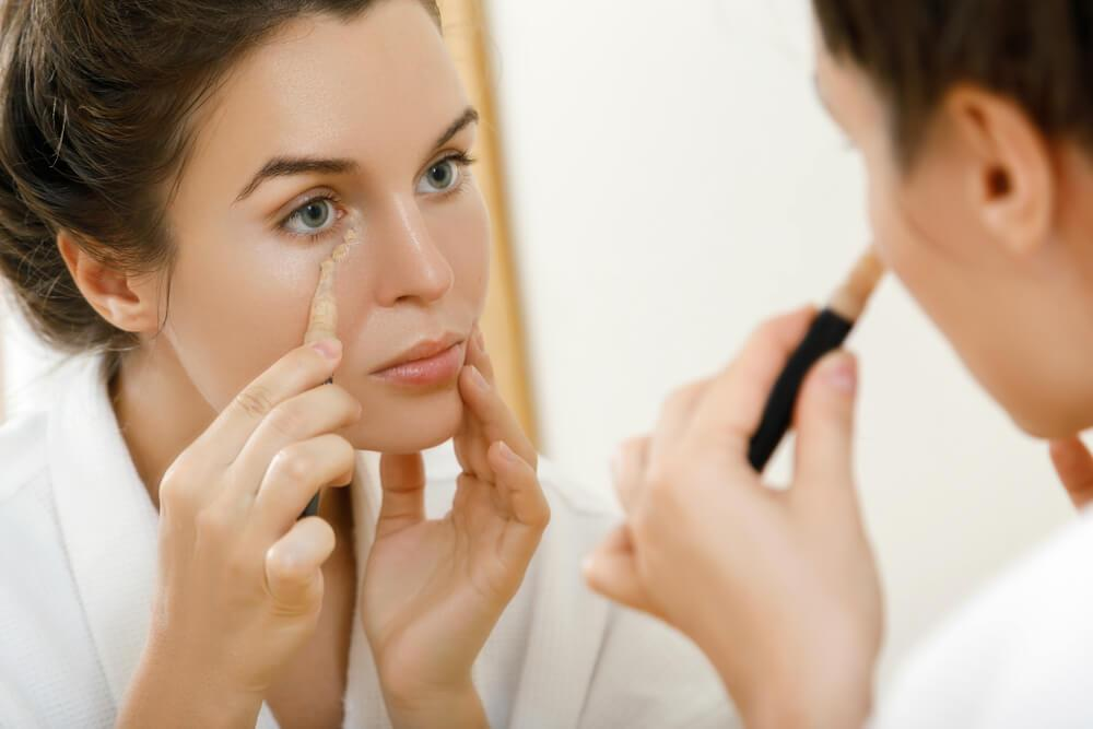 Woman applying concealer under eye