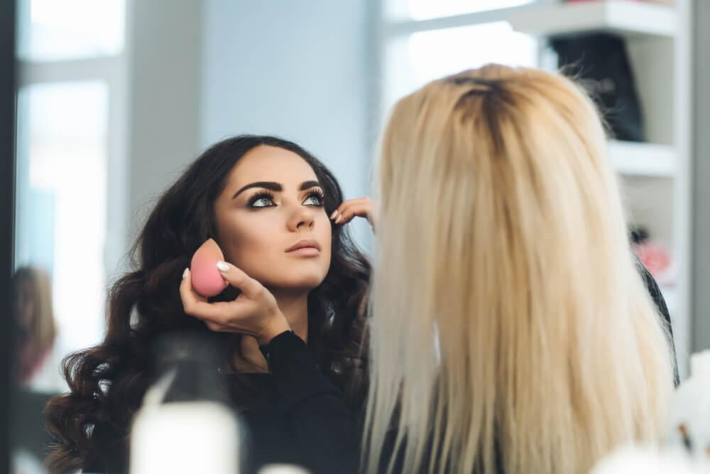 Makeup artist using blender on woman's face