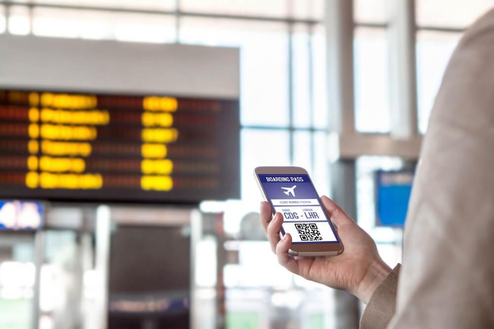 Phone with boarding pass being held up in airport