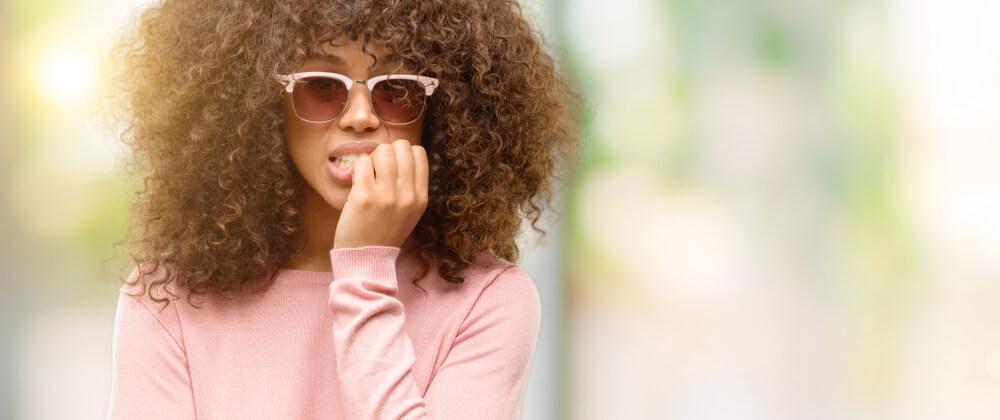 Woman on street biting nails