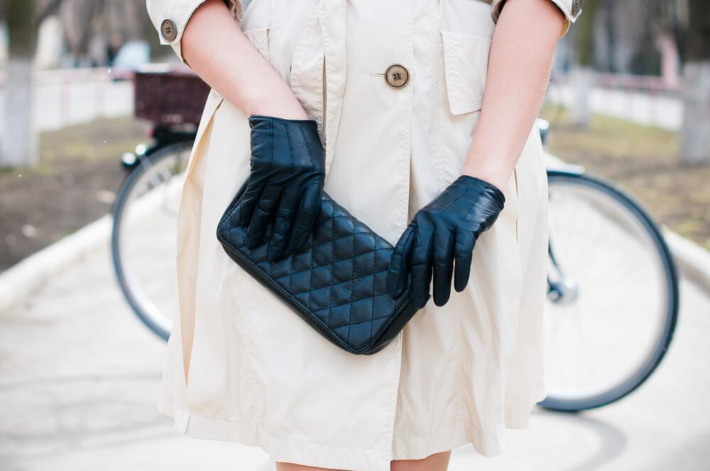 Close-up of stylish woman on street with black gloves and bag