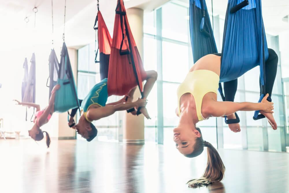 People in studio doing aerial yoga