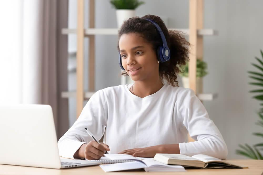 Woman with headphones looking at laptop and taking notes