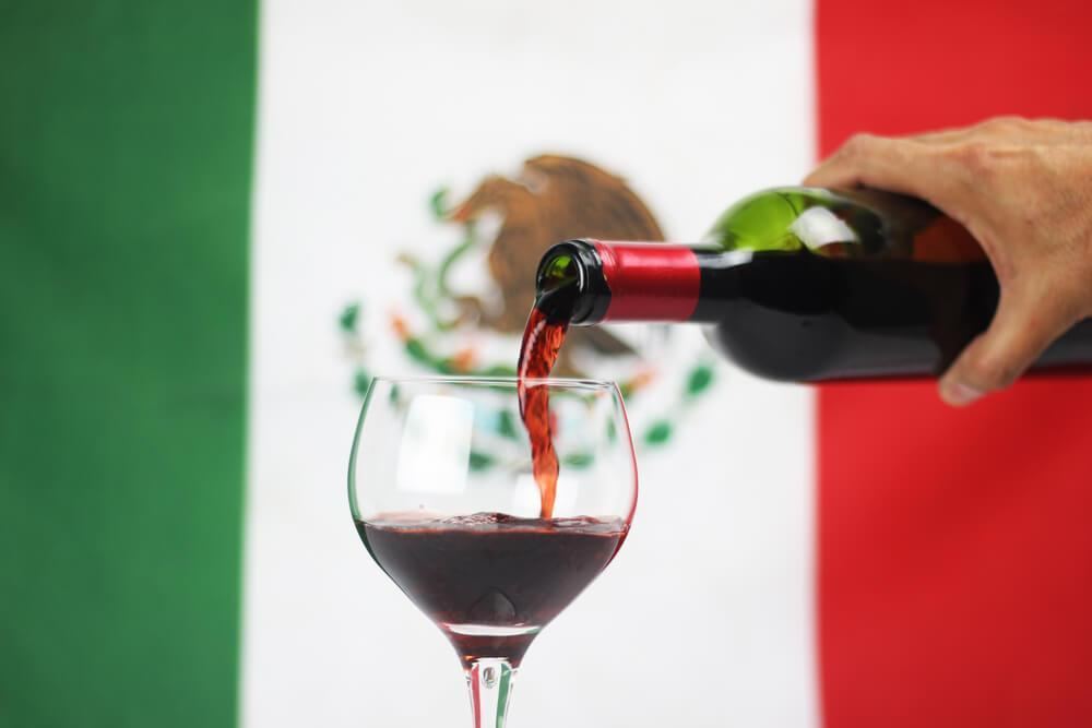Pouring wine in front of Mexican flag