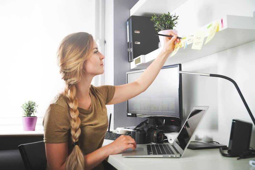 Woman writing note at desk