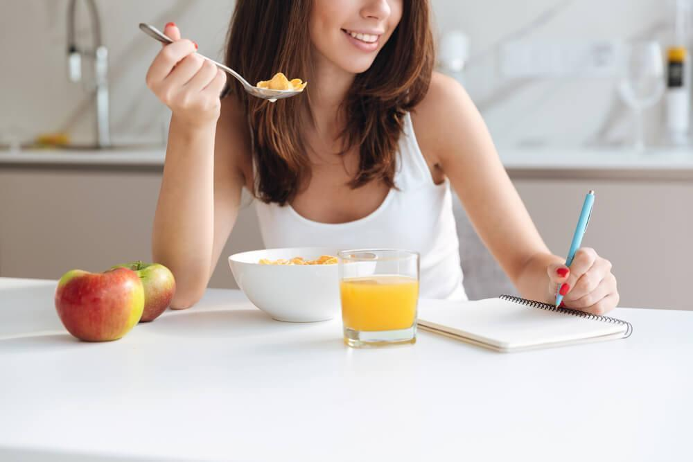 Woman writing while eating