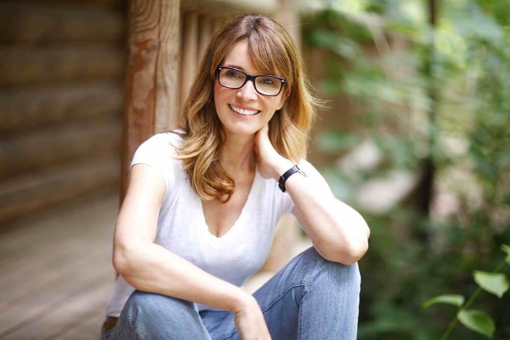 Smiling woman with glasses sitting on a verandah