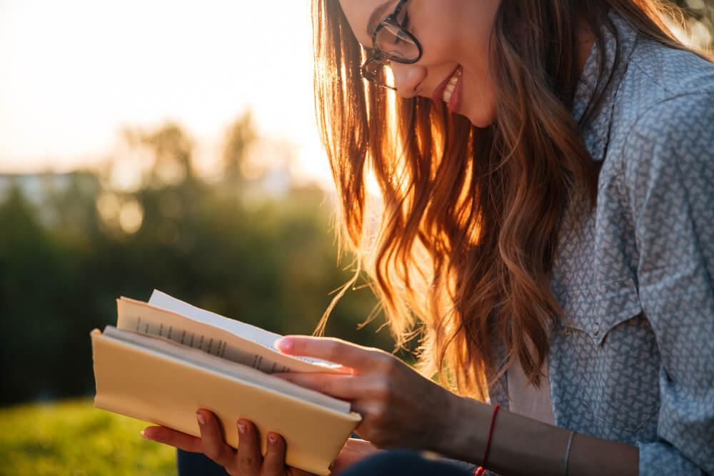 Young woman reading outdoors in the sun