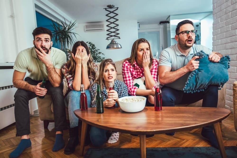 A group of five friends watching TV